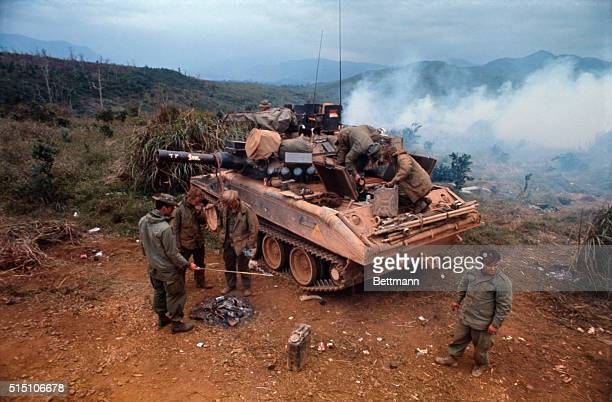 American soldiers look through and stand around a M551 Sheridan tank atop a hill during Operation Dewey Canyon II/Lam Son 719 which is aimed to...