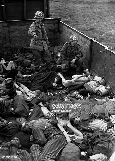 American soldiers look through piles of starved bodies in a goods wagon at Dachau