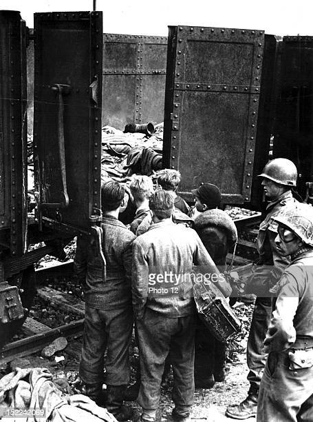 American soldiers make these boys suspected of being members of the Hitler Youth movement examine the box cars filled with dead prisoners in Dachau...
