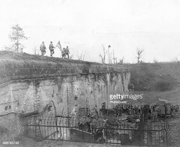 American soldiers of the 101st Inf Regt 26th Division carry American flag which is to be raised over Fort Jeanne d'Arc the Last German fort to...