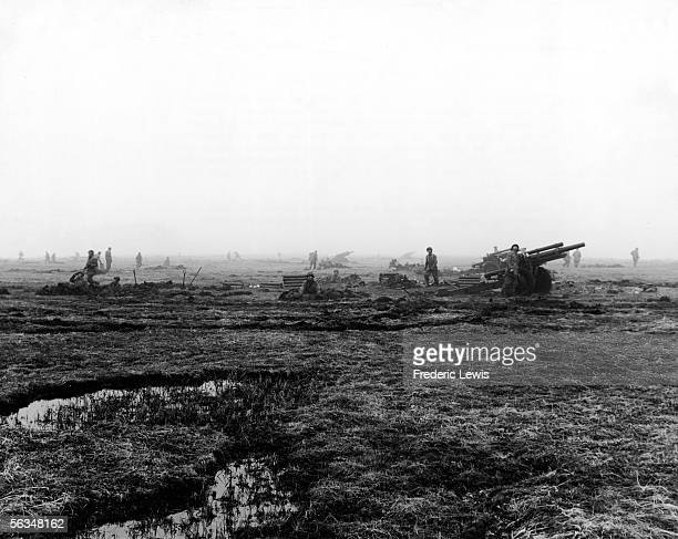 American soldiers on guard in a muddy field look towards the hills for hiding Japanese troops at Attu in the Aleutian Islands Alaska May 11 1943 The...