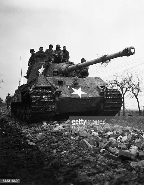American soldiers ride a repaired German Tiger tank down a road Germany December 15 1944
