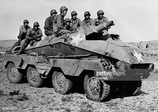 American soldiers ride in a German tank destroyer captured by the Second US Army Corps from the 10th German Panzer Division in the battle of Tunisia...