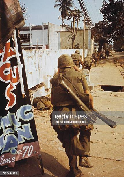American soldiers run along a street using a wall as cover from enemy fire during the Battle of Hue part of the Tet Offensive in the Vietnamese city...