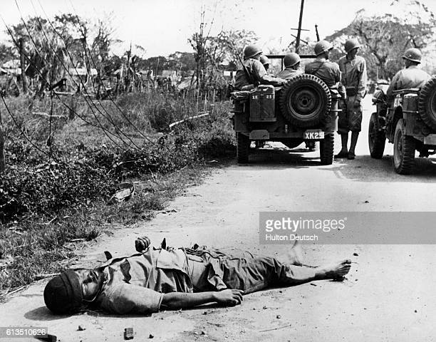 American soldiers sit in their jeeps on the road to Manila A dead Japanese soldier possibly from a tank regiment or a paratroop regiment lies by the...