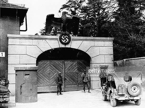 American [] soldiers stand in front of the gate of Dachau Concentration Camp in Dachau Germany A large statue of an eagle and the Nazi swastika are...