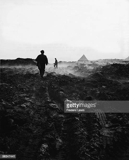 American soldiers trudge through muddy ground near tents of the American base at Attu in the Aleutian Islands Alaska July 29 1943 Tire tracks and...