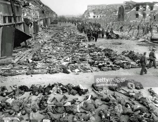 American soldiers walk by row after row of corpses lying on the ground beside barracks at the Nazi concentration camp KZ MittelbauDora at Nordhausen...