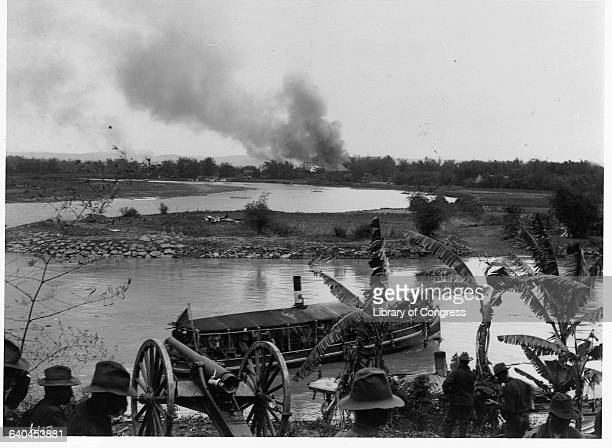 American soldiers watch a boat on a river during the Philippine Insurrection, an uprising in response to America's colonization of the area following...