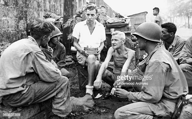 American soldiers who were part of the liberation of the Japanese Bilibid POW camp stop to talk with two internees who had been in the prison camp...