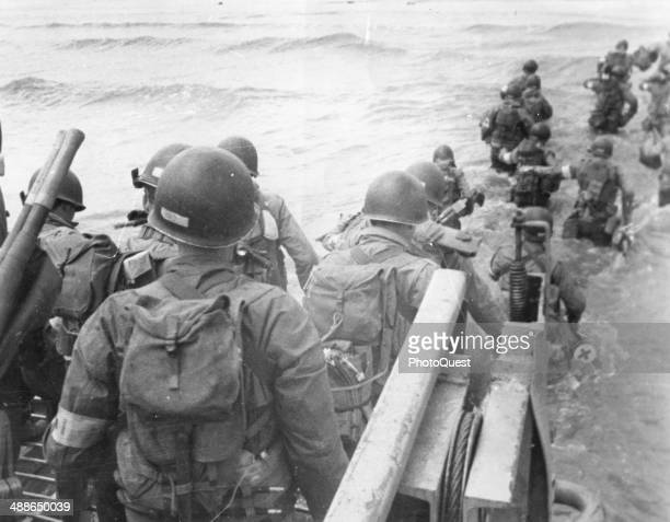 American soldiers with full equipment leap into the surf from a landing craft and wade toward Utah Beach France June 6 1944