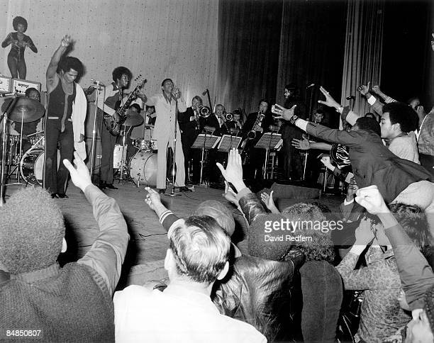 Photo of James BROWN and AUDIENCE and Bobby BYRD and Bootsy COLLINS w/ Bootsy Collins on bass Bobby Byrd in light suit at microphone performing live...