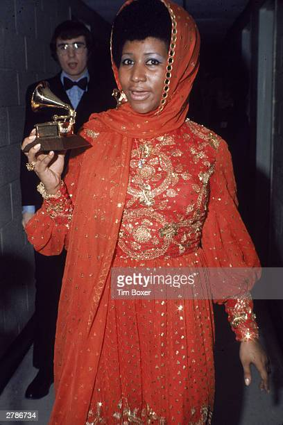 American soul singer Aretha Franklin stands backstage wearing an gold embroidered gown and holding a Grammy Award, circa 1970.