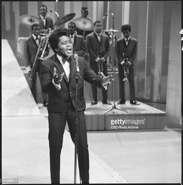 American soul singer James Brown sings on The Ed Sullivan Show as his back up band watches, New York, May 1, 1966.
