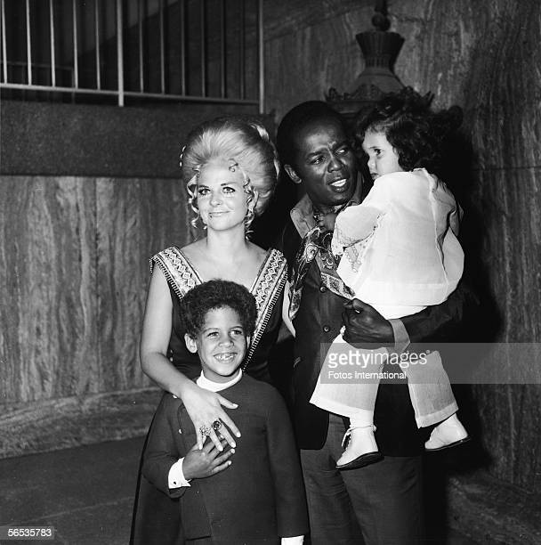 American soul singer Lou Rawls holds his daughter Louanna as his wife Lana Jean and son Lou Jr stand with him at the opening of his stint at the...