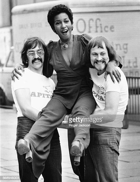 American soul singer Marsha Hunt being lifted up by Capital Radio Breakfast Show disc jockeys Tommy Vance and Dave Symonds to promote her new soul...
