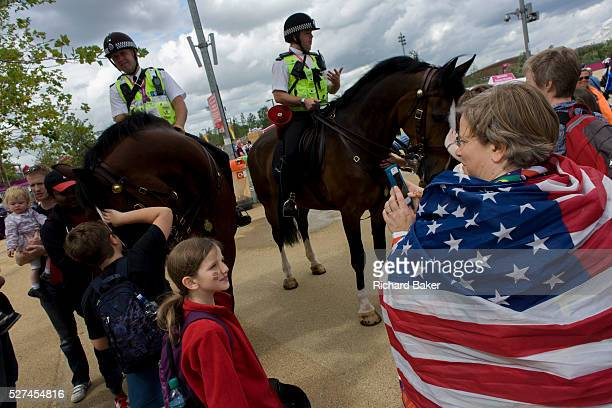 American spectators admire mounted police officers on horseback help control crowds and provide security in the Olympic Park during the London 2012...