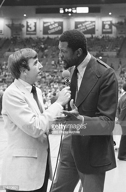 American sportscaster Brent Musburger interviews former professional basketball player and head coach Bill Russell on the court during a basketball...