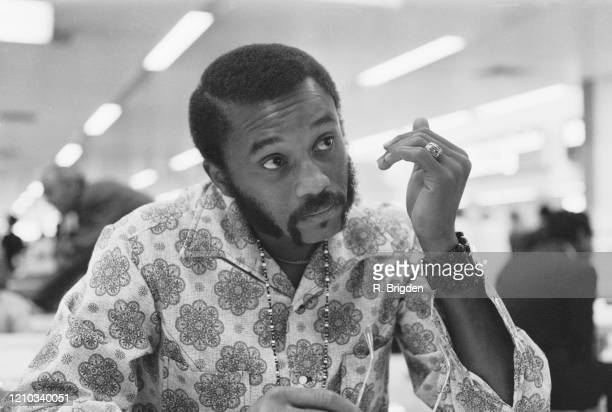 American sprinter and American Football wide receiver Tommie Smith wearing a patterned shirt beaded necklace and cuff bracelet at Heathrow Airport in...