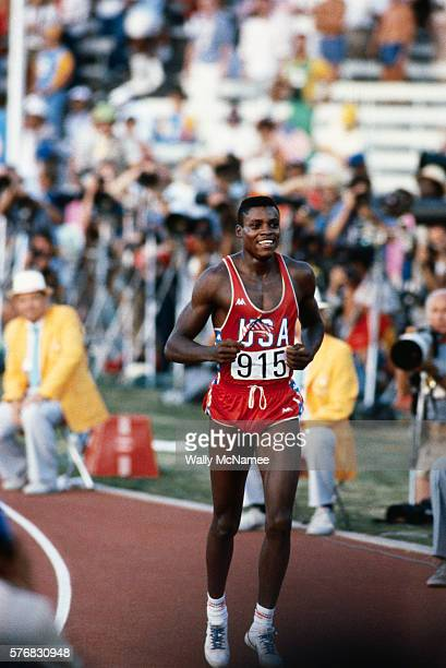 American sprinter Carl Lewis takes a victory lap after winning the Gold Medal in the men's 100 meter dash at the 1984 Olympic Summer Games in Los...