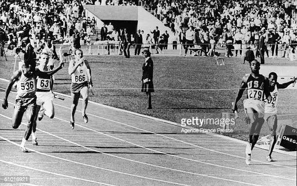American sprinter Jim Hines finishes first in the men's 100 meter relay setting a world record with his teammates Charlie Greene Mel Pender and...