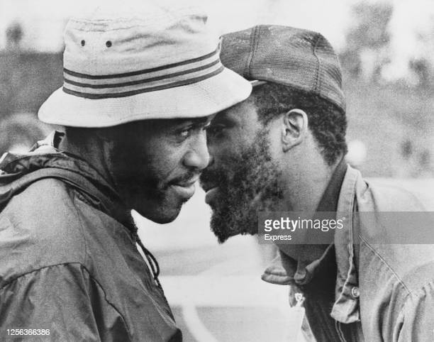American sprinter Lee Evans, wearing a bucket hat, in conversation with American sprinter John Carlos at the 1972 Summer Olympics in Munich, Germany,...