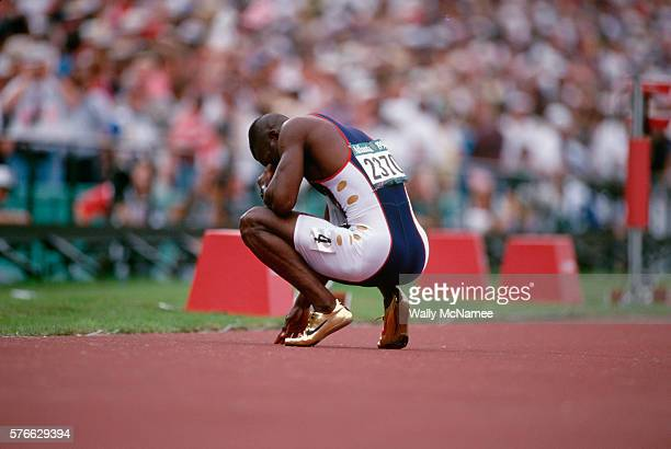 American sprinter Michael Johnson squats on the track holding his head in his hands for a moment of reflection after winning the 200 meter race in...