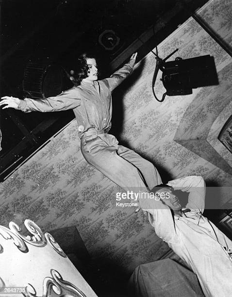 American stage and film actress Katharine Hepburn balancing on the shoulders of British born American actor Cary Grant They are practising for an...