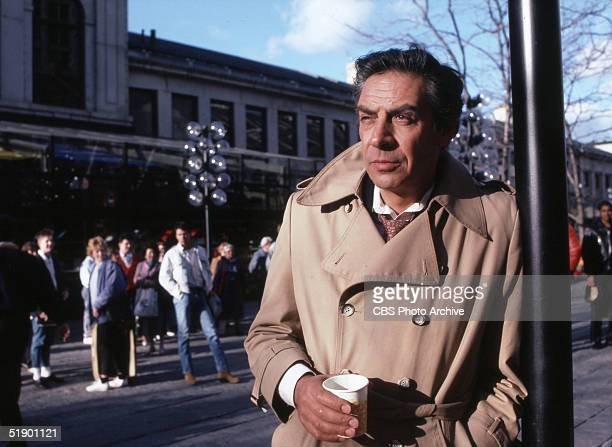American stage and television actor Jerry Orbach leans against a pole with a cup of coffee in his has as the title character in the television show...