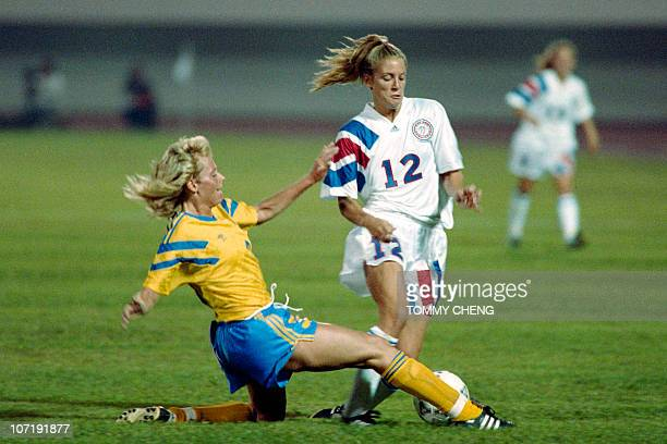 American striker Carin Jennings tries to avoid the tackle of Swede Anette Hansson during their Group B opening match in the inaugural match in...