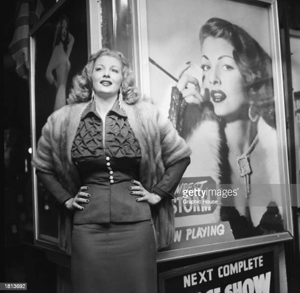American stripper Tempest Storm poses next to a promotional poster for her burlesque act in front of a theater 1954