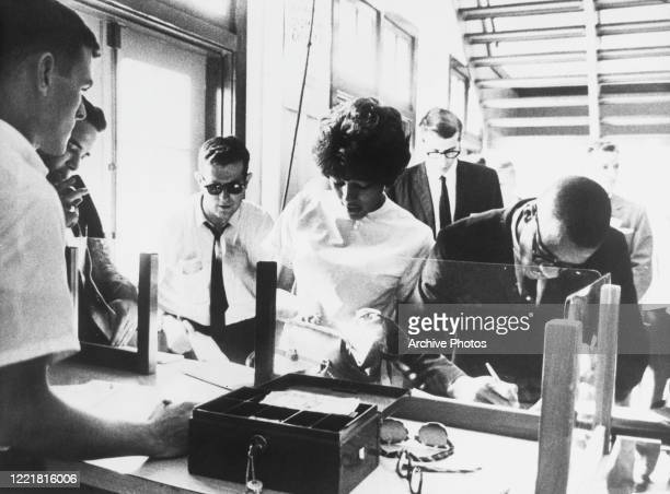 American students Vivian Malone and James Hood pay their registration fees at the Foster Building Registrar's Office, becoming the first African...