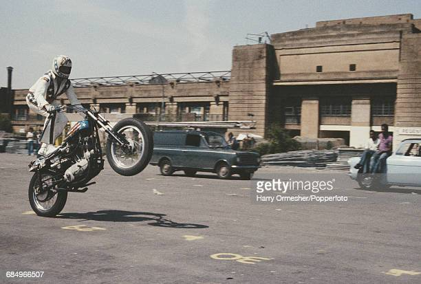 American stunt motorcyclist and entertainer Evel Knievel pictured performing a wheelie whilst riding on the back of his motorcycle in front of the...