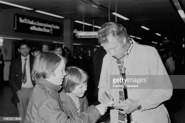 American stunt performer and entertainer Evel Knievel signing autographs to two boys while at the airport UK 9th May 1975