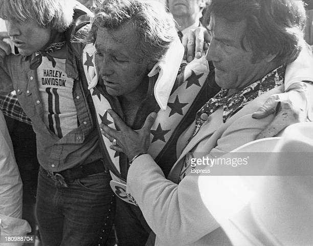 American stunt person Evel Knievel is helped to his feet after crashing during his attempt to jump thirteen buses inside Wembley Stadium London 26th...