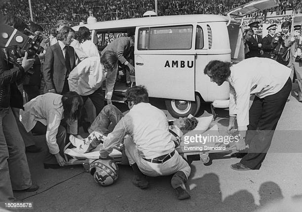 American stunt person Evel Knievel is put on a stretcher after crashing during his attempt to jump thirteen buses inside Wembley Stadium London 26th...