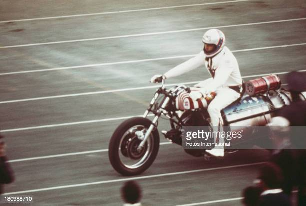 American stunt person Evel Knievel rides a three wheeled motorcycle on an athletics track circa 1977