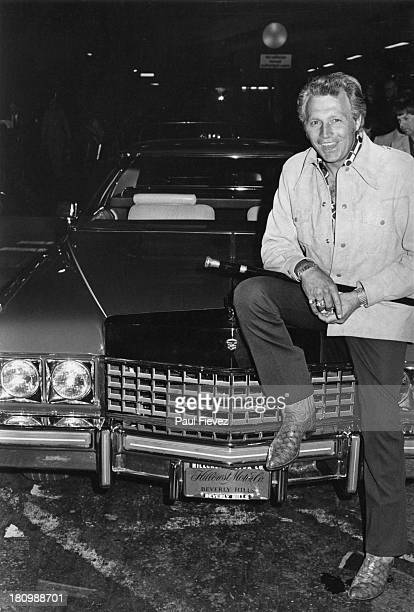 American stunt person Evel Knievel sits on the bonnet of his Cadillac car at Heathrow Airport London 7th July 1975