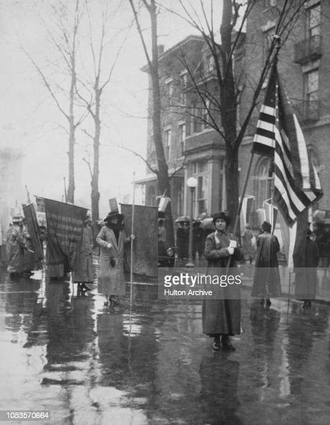 American suffragette and National Women's Party member Eleanor B Arrison walks at the head of a group of suffragettes holding an American flag as...