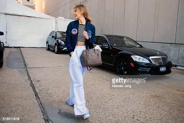 American supermodel Karlie Kloss wears a blue Dolce Gabbana patch bomber jacket Elisabetta Franchi black and white striped crop top white widelegged...