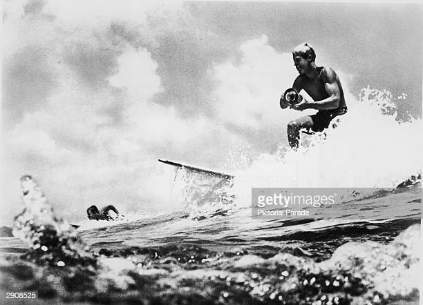American surfer and director Bruce Brown surfs a wave and holds a camera while filming footage for his international surfing documentary 'The Endless...
