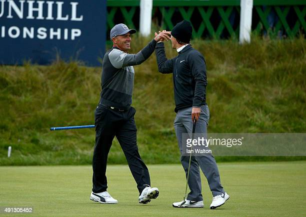 American surfer Kelly Slater is congratulated by his playing partner Thorbjorn Olesen of Denmark after he holes his putt on the 18th green during the...