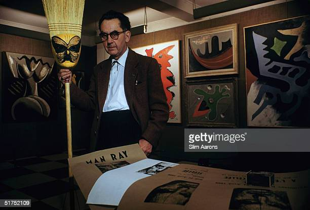 American surrealist artist and photographer Man Ray with some examples of his work at his Left Bank studio in Paris, April 1956.