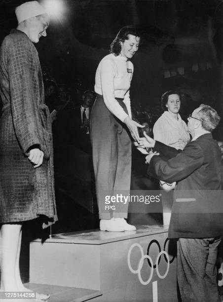 American swimmer Ann Curtis Danish swimmer Greta Andersen being presented with her gold medal by President of the International Swimming Association...