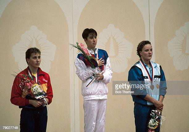 American swimmer Janet Evans of the United States team stands on the podium after coming first to win the gold medal with Noemi Lung of Romania...