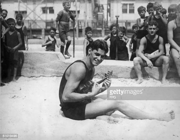 American swimmer Johnny Weissmuller sits on a beach and plays the ukelele for a group of children 1924 Weissmuller won two individual gold medals at...