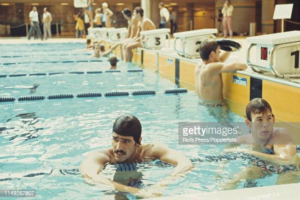 American swimmer Mark Spitz pictured in the pool with two fellow United States swimming team members during competition in a swimming relay event at...