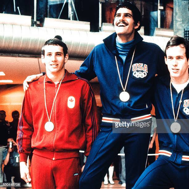 American swimmer Mark Spitz smiles on the podium after winning the gold medal in the 100m butterfly in front of Canadian Bruce Robertson and...