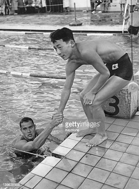 American swimmer Ronald Gora shakes hands with Japanese swimmer Toru Goto in Helsinki during the 1952 Summer Olympics July 1952