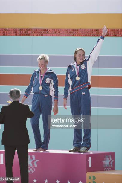 American swimmers Carrie Steinseifer and Nancy Hogshead of the United States team celebrate on the medal podium after finishing in joint first place...